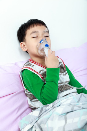sickbed: Asian child closing eyes and holds a mask vapor inhaler for treatment of asthma on sickbed in hospital. Breathing through a steam nebulizer. Concept of inhalation therapy apparatus. Stock Photo