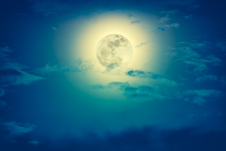 Background of nighttime sky with cloud and full moon with shiny. Natural beauty at night with  beautiful moon behind cloud. Cross process and vintage effect tone. The moon were NOT furnished by NASA.