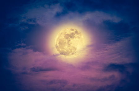Attractive photo of a nighttime sky with clouds and bright full moon. Nightly sky with beautiful full moon. Outdoors at night. Vintage effect tone. The moon were NOT furnished by NASA.