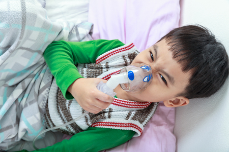 sickbed: Top view of angry asian child holds a mask vapor inhaler for treatment of asthma on sickbed in hospital. Breathing through a steam nebulizer. Concept of inhalation therapy apparatus.
