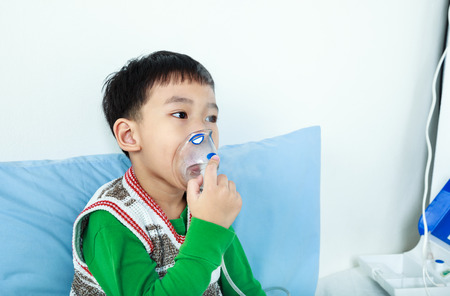 sickbed: Asian child holds a mask vapor inhaler for treatment of asthma on sickbed in hospital. Breathing through a steam nebulizer. Concept of inhalation therapy apparatus.