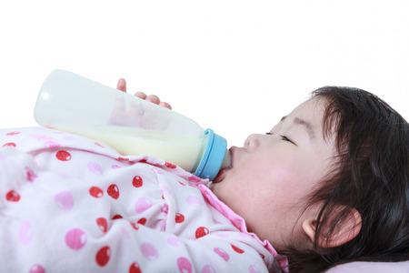 nursing bottle: Closeup cute asian girl sucking up milk bottle at bed on white background. Drinking milk for good health. Stock Photo