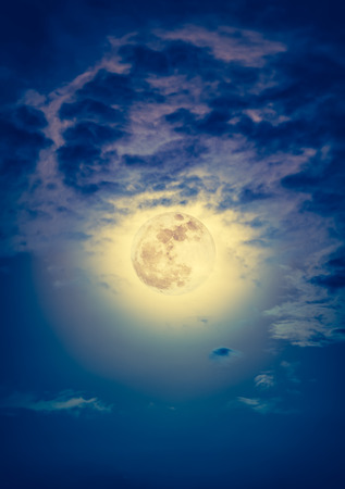 Background of nighttime sky with cloud and bright full moon with shiny. Natural beauty at night with beautiful full moon behind cloud. Vintage effect tone. The moon were NOT furnished by NASA.