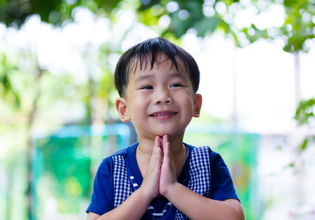 Asian child put the palms of the hands together in salute. Happy little boy tooth smile on blurred bokeh nature background. Outdoor with light on summer day. Children with good humor concepts.