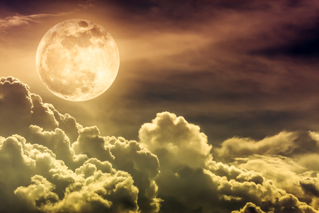 Attractive photo of gold background nighttime sky and bright full moon with shiny. Nightly sky with beautiful full moon and cloudy. Outdoors at night. The moon were NOT furnished by NASA. Stock Photo