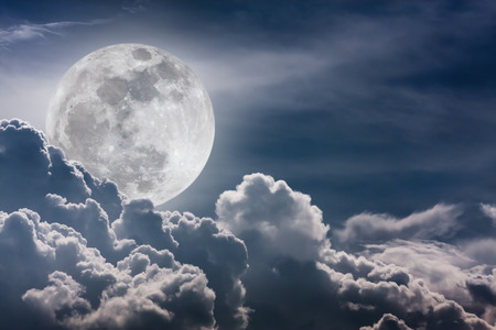 full moon effect: Attractive photo of background nighttime sky with clouds and bright full moon with shiny. Nightly sky with beautiful full moon behind cloud. Vintage effect tone. The moon were NOT furnished by NASA.