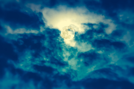 full moon effect: Background of nighttime sky with cloud and full moon with shiny. Natural beauty at night with  beautiful moon behind cloud. Cross process and vintage effect tone. The moon were NOT furnished by NASA.
