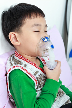 sickbed: Closeup asian child closing eyes and holds a mask vapor inhaler for treatment of asthma on sickbed in hospital. Breathing through a steam nebulizer. Concept of inhalation therapy apparatus.