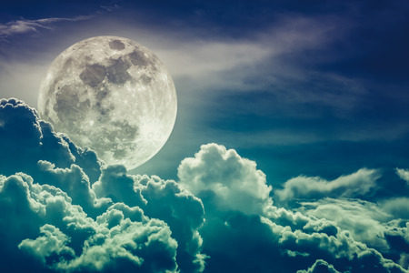 nightly: Attractive photo of background nighttime sky with clouds and bright full moon with shiny. Nightly sky with beautiful full moon behind cloud. Cross process. Stock Photo
