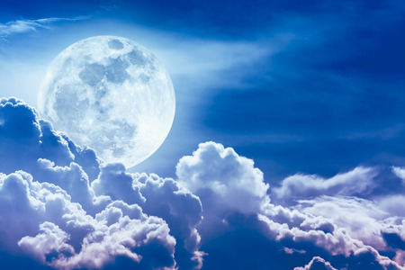 nightly: Attractive photo of blue background nighttime sky with clouds and bright full moon with shiny. Nightly sky with beautiful full moon behind cloud. Outdoors at night.