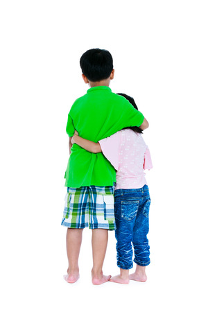 Back view of asian boy put ones arm around sisters shoulder, isolated on white background.  Girl putting her arm around her brothers waist. Concept about loving and bonding of sibling. Studio shot. Stock Photo