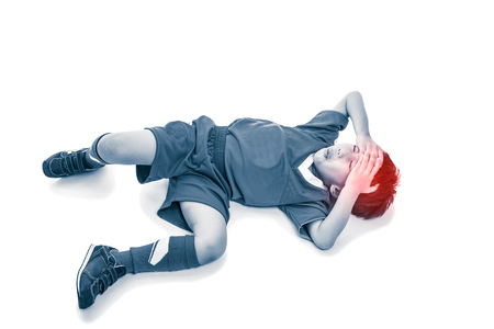 Sports injury. Full body of asian soccer player painful. Child closed eyes and touching his forehead, on white background. Photo with color increase blue skin and red spot indicating location of pain.