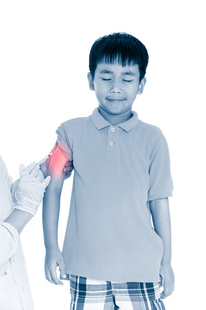 Doctor vaccinating boys arm. Asian illness boy get vaccination or antibiotic in hypodermic syringe. Isolated on white background. Human health care concept. Color increase blue skin and red spot. Stock Photo
