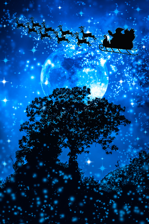 Christmas blue background. Beautiful winter background of snowy night sky, stars, full moon and tree. Silhouette of Santa Claus flying on a sleigh pulled by reindeer. Moon were NOT furnished by NASA.