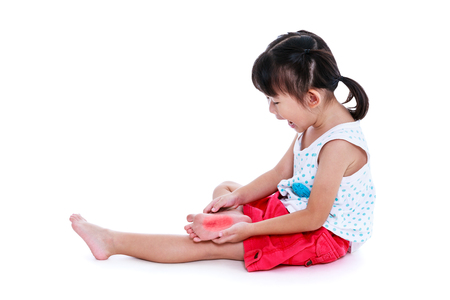 Full body of asian child injured at sole, red spot indicating location of pain. Girl screaming. Isolated on white background with copy space. Studio shot. Human health care and problem concept. Stock Photo