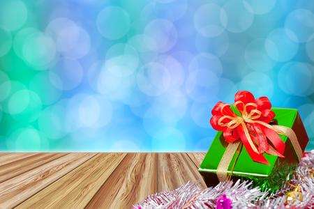 Gift box on perspective wood table with abstract twinkling lights blurred bokeh background for christmas and new year celebration. Stock Photo