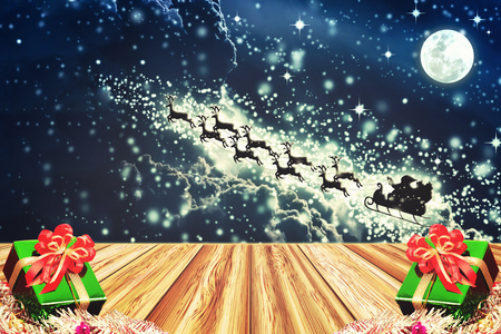 santa sleigh: Gift box on wooden board with Santa Claus on a sleigh pulled by reindeer for christmas and new year background.  Beautiful snowy night sky with stars and full moon. The moon were NOT furnished by NASA Stock Photo