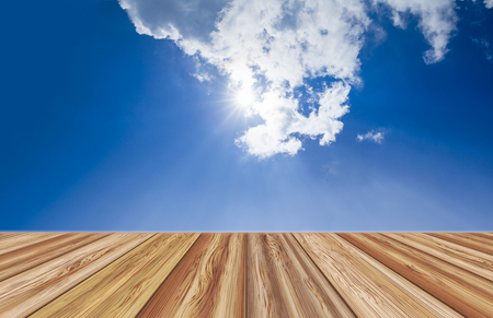 counter top: Perspective wooden board empty table top over beautiful blue sky with clouds and sunlight on summer day. Can be used for montage or display your products. Stock Photo