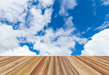 Perspective wooden board empty table top over beautiful blue sky with cloudy at the daytime on summer day. Can be used for montage or display your products.