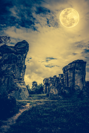 full moon effect: Boulders against sky with clouds and beautiful full moon at night. Outdoors at nighttime. Beauty of nature use as background. The moon were NOT furnished by NASA. Cross process and vintage tone effect. Stock Photo