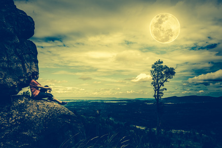 Woman sitting on boulders and looking at  sky with cloudy and beautiful full moon over tranquil nature nighttime. Low key and cross process tone effect. Stock Photo