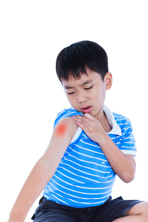 groaning: Closeup of asian child injured at shoulder. Sad boy groaning and looking at bruise with a painful gesture. Isolated on white background. Human health care and problem concept.