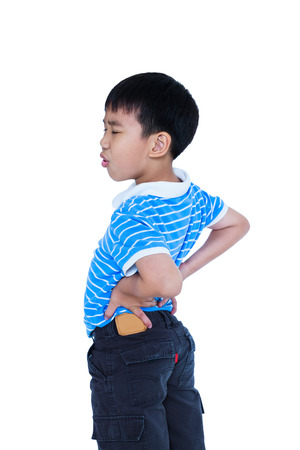 groaning: Asian child rubbing the muscles of his lower back. Isolated on white background. Unhappy boy backache groaning with a painful gesture. Facial expression feeling reaction. Studio shot.