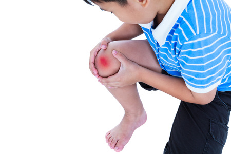 Child injured. Closeup of asian child injured at knee with copy space on left. Sad boy looking at bruise with a painful gesture, isolated on white background. Human health care and problem concept.