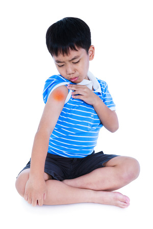 groaning: Full body of asian child injured at shoulder. Sad boy groaning and looking at bruise with a painful gesture. Isolated on white background. Human health care and problem concept.