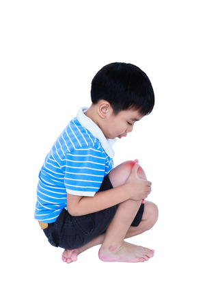 Child injured. Full body of asian child injured at knee. Sad boy sitting and looking at bruise with a painful gesture, isolated on white background. Human health care and problem concept. Studio shot.