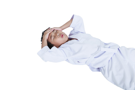 groaning: Accidents in sports. Asian child athletes taekwondo hurt the forehead. Isolated on white background. Boy lie down and groaning with a painful gesture. Studio shot.