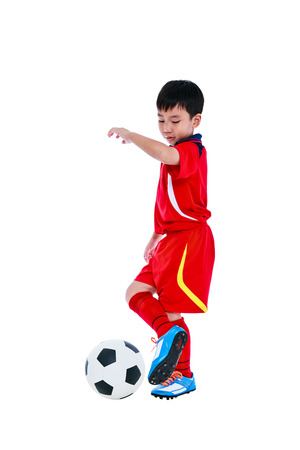 Full length portrait of happy asian soccer player in red uniform playing his soccer ball. Healthy lifestyle and sport concepts. Studio shot. Isolated on white background.