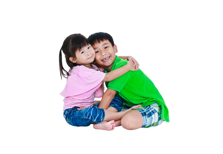 Asian kindly brother sitting and hugging his sister smiling happily. Isolated on white background. Concept about loving and bonding of sibling. Happy family spending time together. Studio shot.