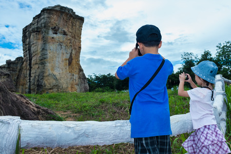 Back view of asian children taking photos by camera at national park . Family relaxing outdoors with bright sunlight at the day time on summer day, travel on vacation. Child in nature. Stock Photo