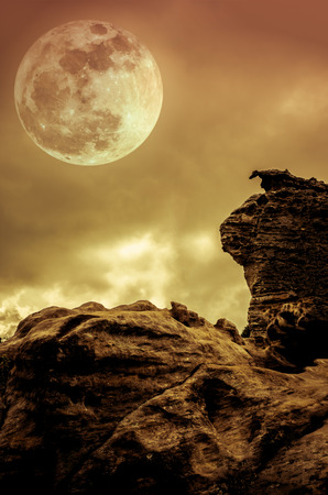 Boulders against gold sky background with clouds and beautiful full moon at night. Outdoors at nighttime. Beauty of nature use as background. Sepia tone.The moon were NOT furnished by NASA.