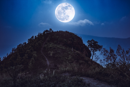 Mountain peak landscape. Walkway to the top of a mountain with blue sky and beautiful full moon over tranquil nature. Beauty landscape at night time. The moon were NOT furnished by NASA Stock Photo