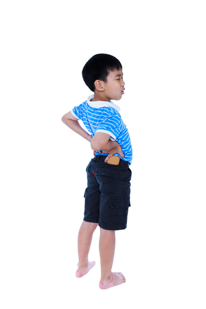groaning: Full body of asian child rubbing the muscles of his lower back. Isolated on white background. Unhappy boy backache groaning with a painful gesture. Facial expression feeling reaction. Studio shot.