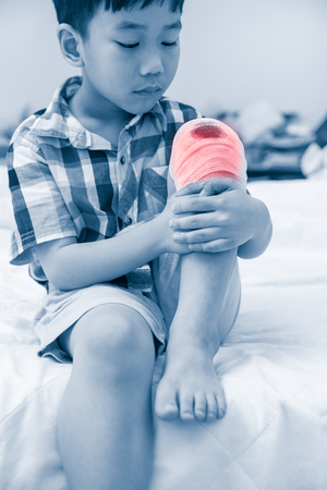 Child injured. Asian boy looking at wound on his knee with bandage, bandage in focus. Children have been an accident. Human healthcare concept. Color increase blue skin and red spot indicating of pain