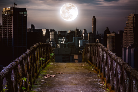 Old concrete bridge with wooden across to skyscrapers with super moon background at night. Dark tone and high contrast style. Vintage tone. The moon were NOT furnished by NASA. Stock Photo