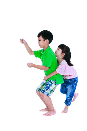 Asian sister standing and hugging his brother smiling happily, isolated on white background. Concept about loving and bonding of sibling. Playful boy driving a train or car. Children role playing. Studio shot. Stock Photo
