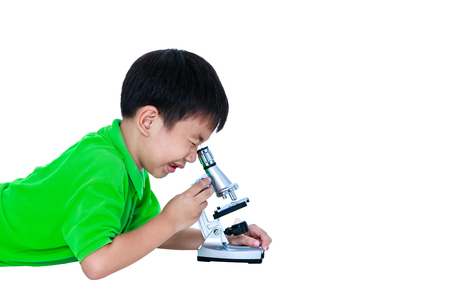 Asian child observed through a microscope biological preparations with copy space. Boy having education activities. Isolated on white background. Studio shot.
