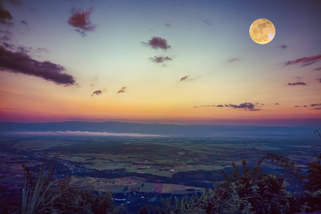 The full moon in the evening after sunset. Scenes from view point with colorful sky. Beautiful full moon over tranquil nature. Outdoors at nighttime. Vintage tone. The moon were NOT furnished by NASA. Stock Photo