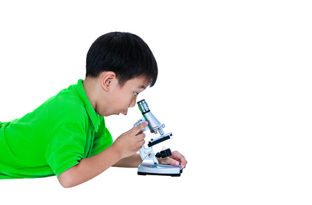 Child surprised. Asian boy observed through a microscope biological preparations with copy space. Boy having education activities. Isolated on white background. Studio shot.