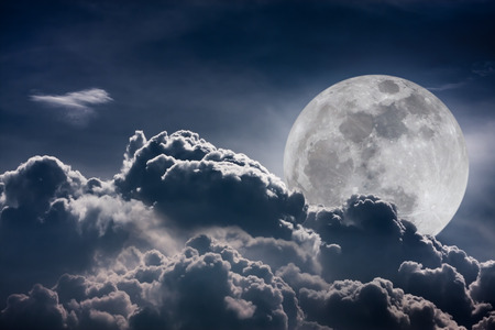 Super moon. Attractive photo of background night sky with cloudy and bright full moon. Nightly sky with beautiful full moon behind clouds. Vintage tone effect. Stock Photo