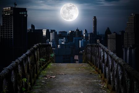 古いコンクリート橋夜スーパー月背景の高層ビルに木製。暗いトーンとコントラストの高いスタイル。月は、NASA によって供給されたないです。 写真素材