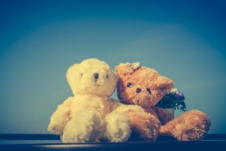 빈티지 음색 테이블, 푸른 하늘 배경에 앉아 두 아름 다운 인형의 이미지. 개념 곰 사랑과 발렌타인 하루에 대 한 관계. 인사말 또는 선물 카드 디자인