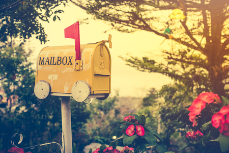 Old yellow stained metal mailbox has red flag raised up to indicate mail has arrived. Outdoor on summer day with bright sunlight at sunset. Vintage effect tone. Stock Photo