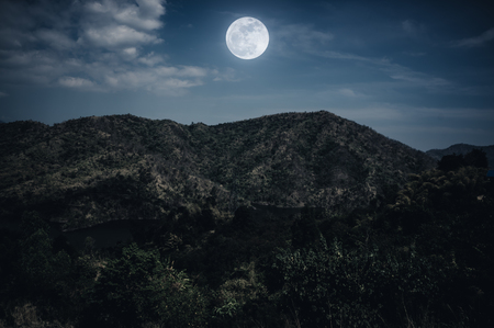 Landscape of night sky and cloudy above mountain peak. Beautiful bright full moon over tranquil nature on dark tone. The moon were NOT furnished by NASA.