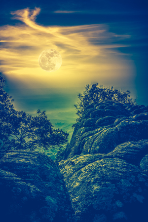 Landscape of night sky with beautiful bright  full moon above view point on the top of mountain, serenity nature background. Cross process and vintage effect tone. The moon taken with my own camera. Stock Photo