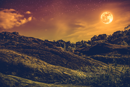 Landscape of sky with many stars and beautiful full moon over tranquil nature background. Outdoor at nighttime. Vintage and sepia tone. The moon taken with my own camera. Stock Photo